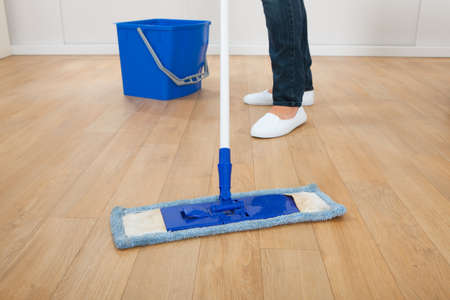 Low section of young woman mopping hardwood floor at home Foto de archivo
