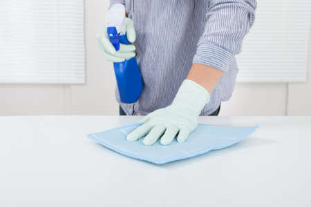 wipe: Closeup of womans hand wiping table with rag at home