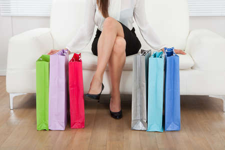 Low section of businesswoman sitting on sofa with multicolored shopping bags on floor at home photo