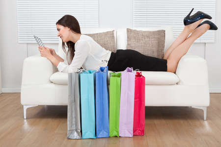 Full length side view of young businesswoman using digital tablet with shopping bags on floor at home photo