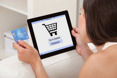 shopping lady: Young woman with credit card shopping online on digital tablet while lying at home Stock Photo