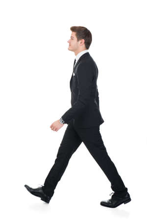 Full length side view of confident businessman walking against white background Imagens