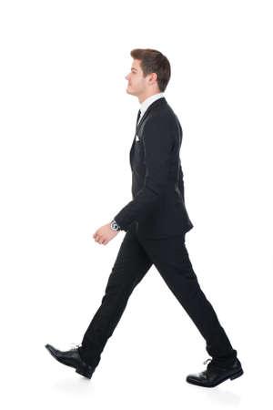 Full length side view of confident businessman walking against white background Foto de archivo