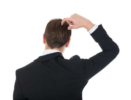 Rear view of confused businessman scratching his head over white background photo