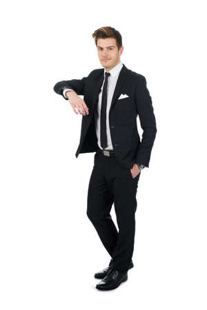 Full length portrait of confident young businessman leaning on invisible wall over white background photo