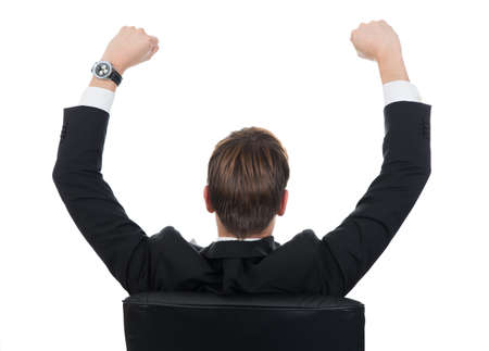 arms raised: Rear view of successful businessman with arms raised sitting on chair on white background Stock Photo