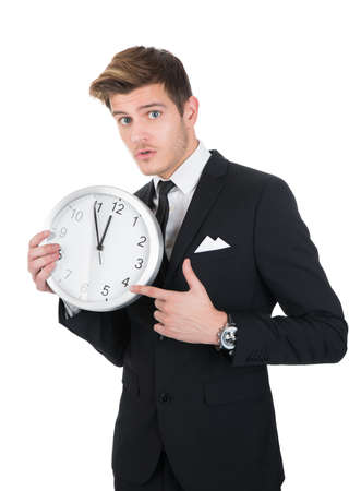 punctual: Portrait of young businessman pointing at clock against white background