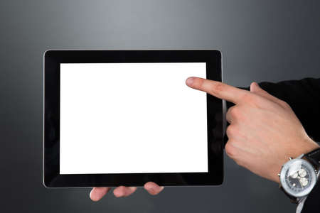 Cropped image of businessman holding digital tablet with blank screen over gray background photo