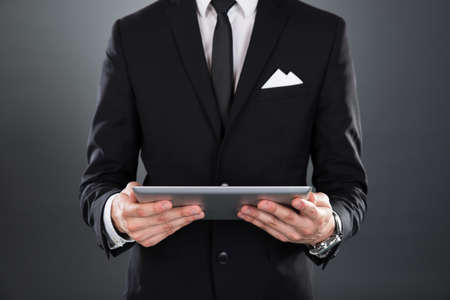 Midsection of businessman holding digital tablet over gray background photo