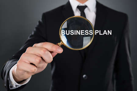 Midsection of young businessman showing Business Plan word through magnifying glass against gray background photo