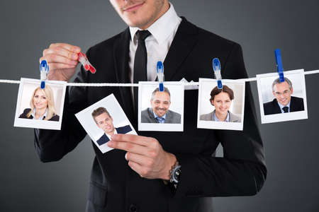 Midsection of businessman selecting candidate from clothesline against gray background