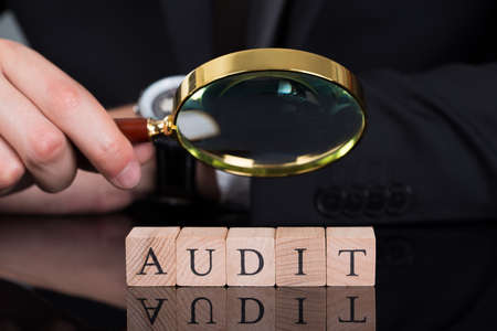 Midsection of young businessman examining Audit blocks through magnifying glass on desk photo