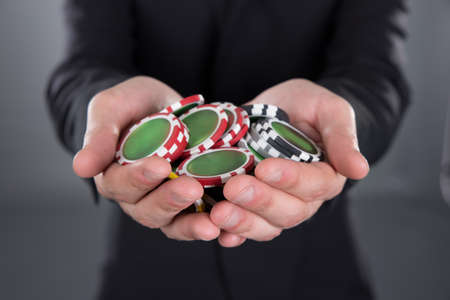 hands cupped: Midsection of businessman holding poker chips in cupped hands against gray background Stock Photo