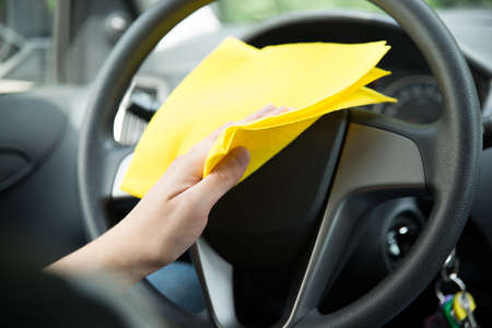rag wheel: Mans hand cleaning steering wheel of car with yellow microfiber cloth