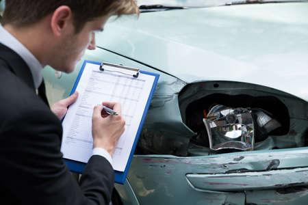 Side view of writing on clipboard while insurance agent examining car after accident Standard-Bild