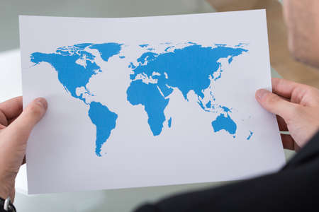 worldmap: Cropped image of businessman holding world map in office