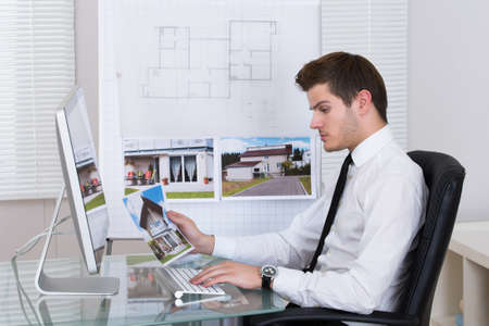Side view of real estate agent working on computer in office Stockfoto