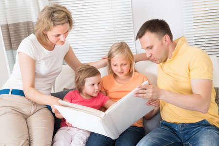 indoor photo: Family Looking At Photos In Photobook At Home Stock Photo