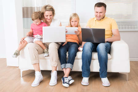 Family Using Tablets and Computers At Home Stock Photo