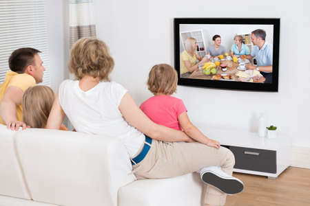 woman watching tv: Familia joven que ve la TV junto en el pa�s