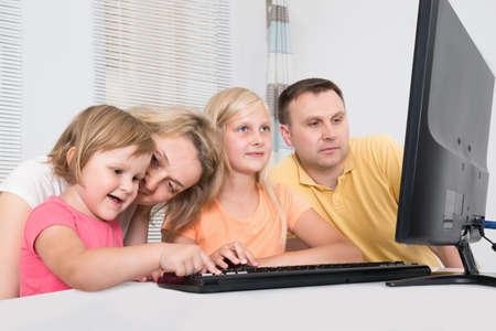 niños jugando videojuegos: Familia joven que usa el ordenador junto en el país Foto de archivo