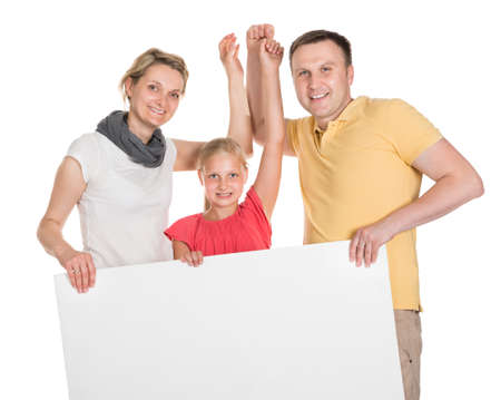 Happy Young Family Holding Banner. Isolated On White Stock Photo