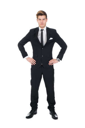 arms akimbo: Full length portrait of confident young businessman standing with hands on hips over white background