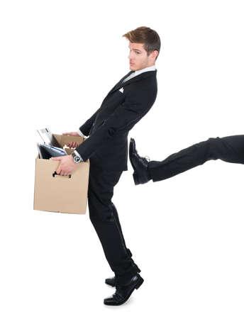 Volledige lengte van zakenman die kartonnen doos met been schoppen hem tegen een witte achtergrond