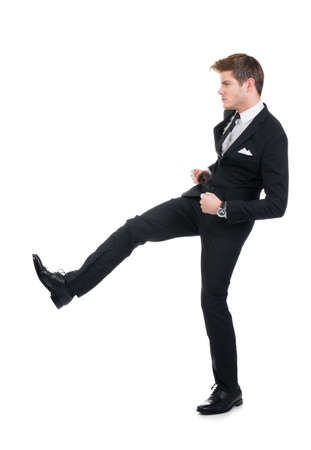 Full length of angry businessman kicking against white background