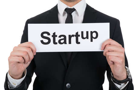 commencing: Midsection of businessman holding Startup sign over white background Stock Photo