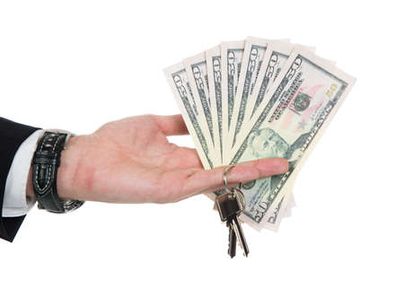 Cropped image of businessmans hand holding dollar bills and key over white background photo