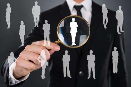 job interview: Midsection of businessman searching candidate with magnifying glass over gray background Stock Photo