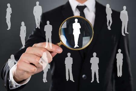 Plavte podnikatel hledá kandidáta s lupou nad šedé pozadí Reklamní fotografie