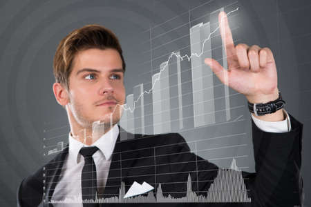 investment analysis: Young businessman touching transparent screen with growing bar graph over gray background