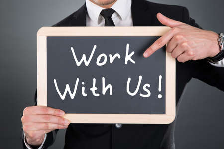 hiring: Midsection of young businessman pointing Work With Us sign on slate over gray background Stock Photo