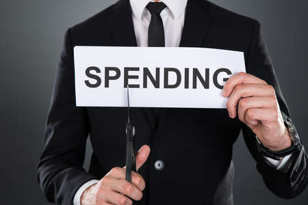 cutting costs: Midsection of businessman cutting the word Spending on paper with scissors over gray background