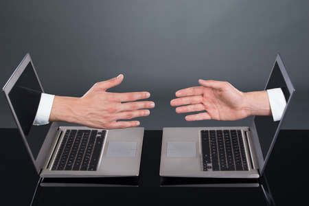 Businessmens hands emitting from laptops representing deal over gray background photo