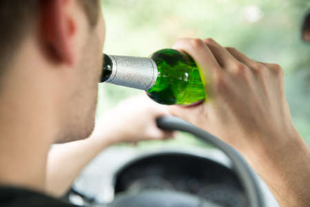 drinking driving: Cropped image of man drinking alcohol while driving car