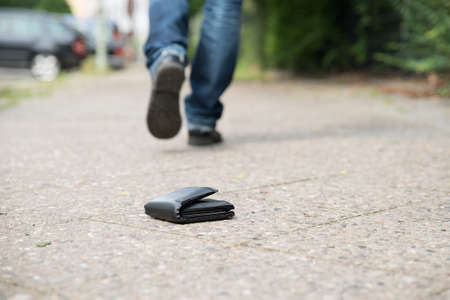 Lage deel van man lopen tegen gevallen portefeuille op straat