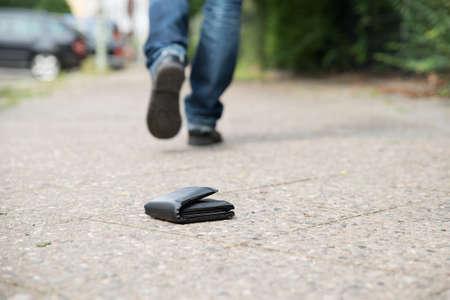 people walking: Low section of man walking against fallen wallet on street
