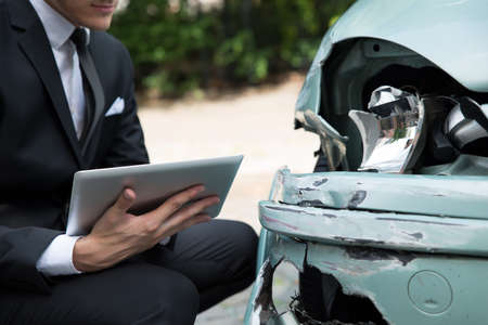 reclamo: Vista lateral de escrito en el portapapeles, mientras que el examen de agente de seguros de coche despu�s de un accidente Foto de archivo