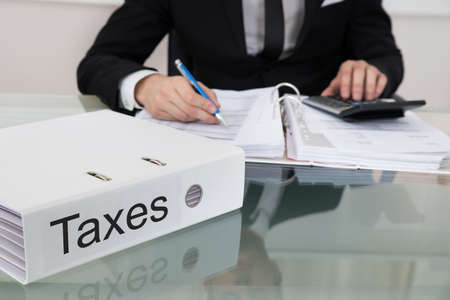 taxation: Midsection of businessman calculating taxes at desk in office