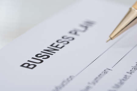 Cropped image of pen business plan form on desk photo
