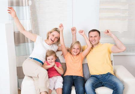 family sofa: Cheering Family Sitting On Sofa At Home