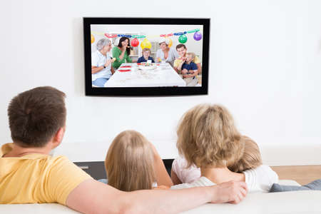 personas viendo tv: Familia joven que ve la TV junto en el pa�s