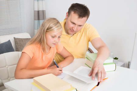 Father Helping Daughter With Homework At Home photo