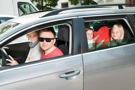 Familia feliz que viajan en coche. Disparo al aire libre