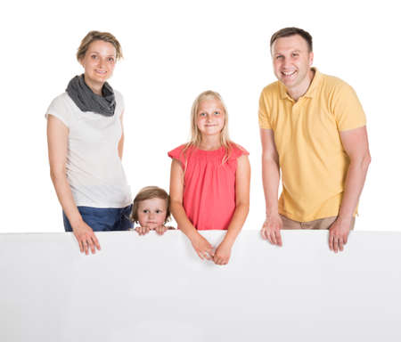Happy Young Family Holding Banner. Isolated On White photo
