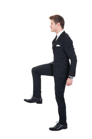 subiendo escaleras: Vista lateral de cuerpo entero de hombre de negocios subir escaleras imaginarias contra el fondo blanco