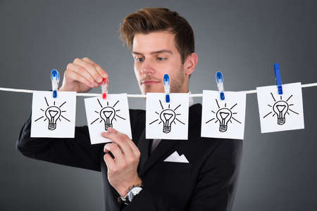 pinning: Young businessman pinning papers lightbulbs on clothesline against gray background Stock Photo